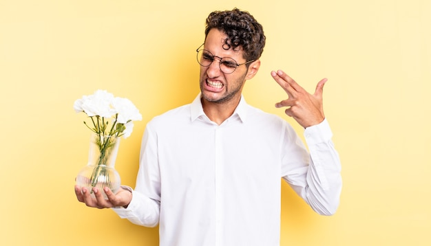 Hispanic handsome man looking unhappy and stressed, suicide gesture making gun sign. flowers pot concept