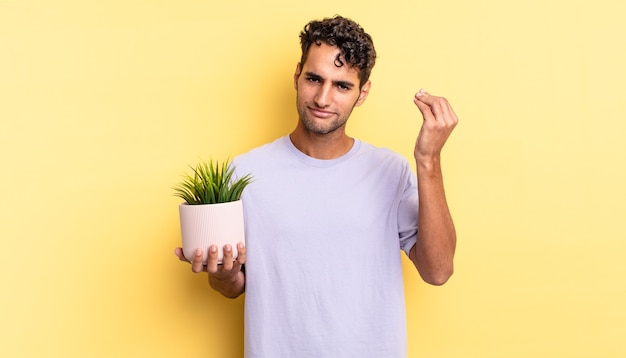 ヒスパニック系のハンサムな男が、お金を払うように言って、身振りやお金のジェスチャーをします。装飾的な植物の概念