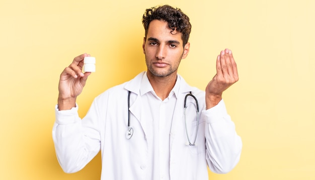 ヒスパニック系のハンサムな男が、お金を払うように言って、身振りやお金のジェスチャーをします。医師のボトルの丸薬の概念