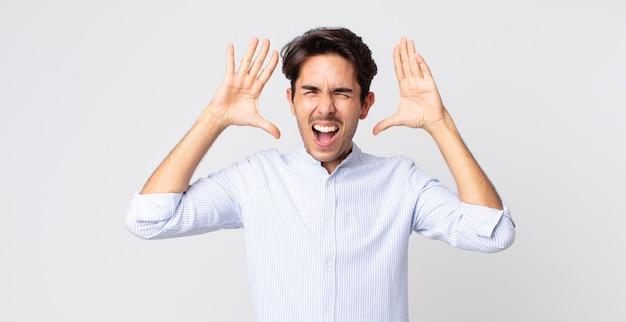 히스패닉 잘 생긴 남자는 머리 옆에 손을 놓고 공황이나 분노, 충격, 겁에 질린 또는 분노에 비명