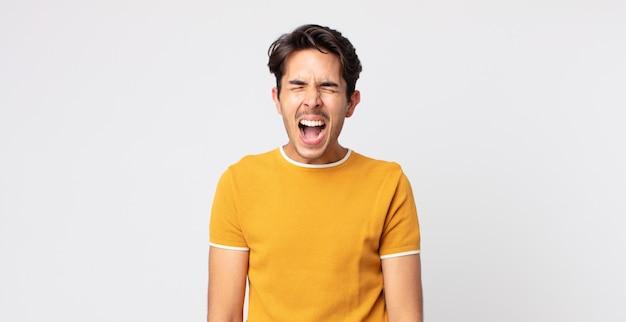ヒスパニック系のハンサムな男が積極的に叫び、非常に怒っている、イライラしている、憤慨している、またはイライラしているように見えます。