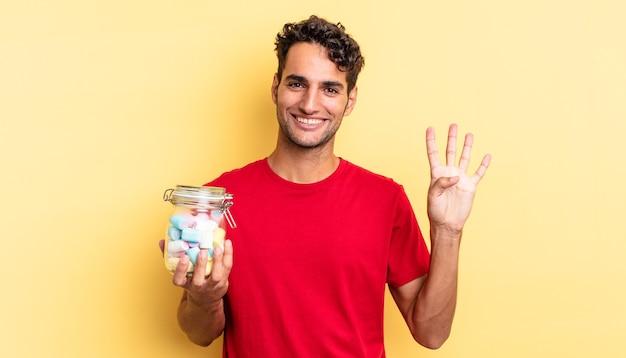 Латиноамериканский красивый мужчина улыбается и выглядит дружелюбно, показывая номер четыре. концепция конфет