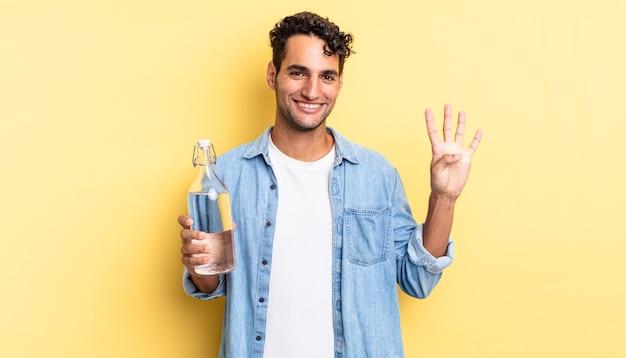 Латиноамериканский красивый мужчина улыбается и выглядит дружелюбно, показывая номер четыре. концепция бутылки с водой
