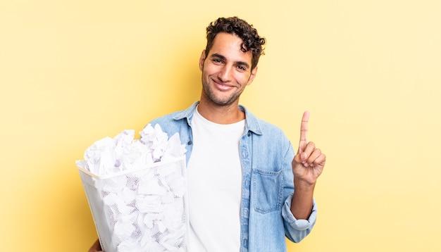 Латиноамериканский красивый мужчина улыбается и выглядит дружелюбно, показывая номер один. бумажные шары мусор концепция