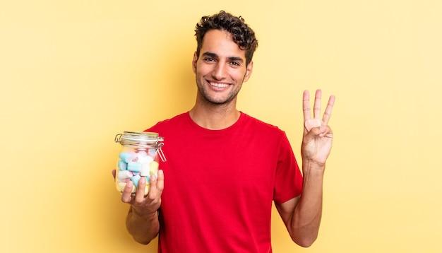 ヒスパニック系のハンサムな男が笑顔でフレンドリーに見え、3番目を示しています。キャンディーのコンセプト