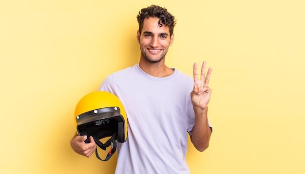 Латиноамериканский красивый мужчина улыбается и выглядит дружелюбно, показывая номер три. концепция мотоциклетного шлема
