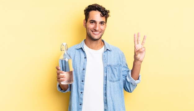 ヒスパニック系のハンサムな男が笑顔でフレンドリーに見え、3番目を示しています。ウォーターボトルのコンセプト