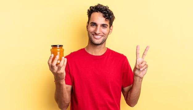 Латиноамериканский красивый мужчина улыбается и выглядит дружелюбно, показывая номер два. персиковое варенье