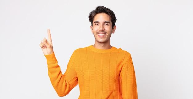スペースをコピーするために片手で上向きに元気にそして幸せに笑って、ヒスパニック系のハンサムな男