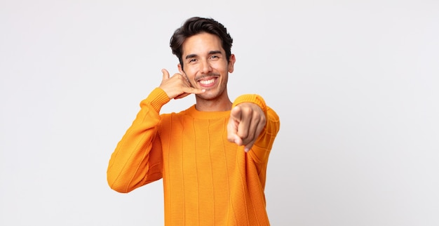 히스패닉 잘생긴 남자가 쾌활하게 웃고 카메라를 가리키며 나중에 전화를 걸고 전화 통화를 합니다.
