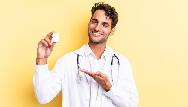 Испаноязычный красивый мужчина весело улыбается, чувствует себя счастливым и демонстрирует концепцию. врач бутылку таблетки концепция