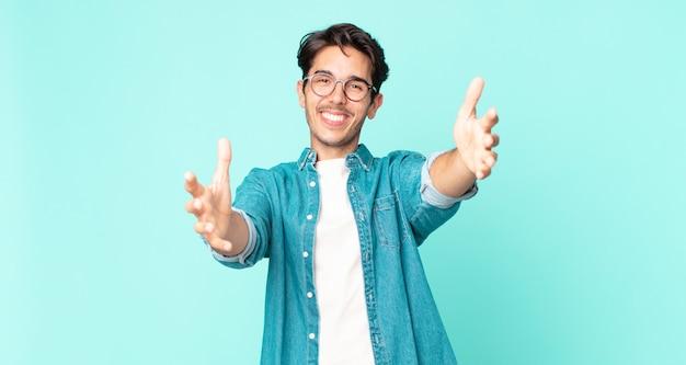 ヒスパニック系のハンサムな男は元気に笑顔で暖かく、フレンドリーで、愛情のこもった歓迎の抱擁を与え、幸せで愛らしい感じ