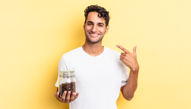 자신의 넓은 미소를 가리키며 자신 있게 웃고 있는 히스패닉 잘생긴 남자. 커피 콩 병