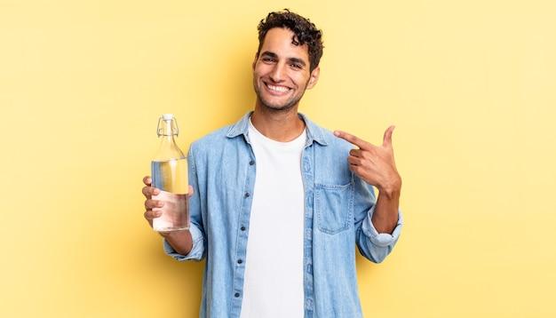 自信を持って笑顔のヒスパニック系ハンサムな男が自分の広い笑顔を指しています。ウォーターボトルのコンセプト