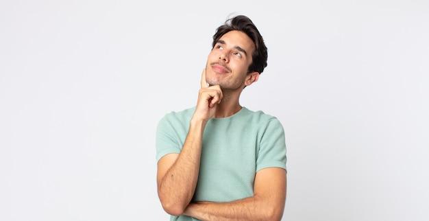 ヒスパニック系のハンサムな男が幸せそうに笑い、空想や疑念を抱き、横を向いている