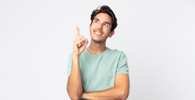 ヒスパニック系のハンサムな男は幸せそうに笑って横向きに、疑問に思ったり、考えたり、アイデアを持っている