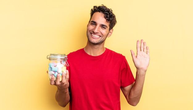 幸せに笑って、手を振って、あなたを歓迎し、挨拶するヒスパニック系のハンサムな男。キャンディーのコンセプト