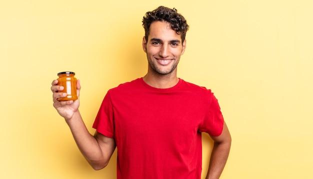 Латиноамериканский красивый мужчина счастливо улыбается, положив руку на бедро и уверенно. персиковое варенье