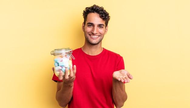 ヒスパニック系のハンサムな男は、フレンドリーで幸せに笑って、コンセプトを提供し、示しています。キャンディーのコンセプト