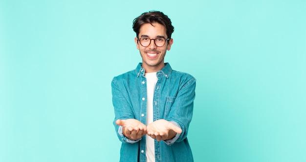 フレンドリーで自信に満ちた、前向きな表情で幸せそうに笑って、オブジェクトやコンセプトを提供し、示すヒスパニック系のハンサムな男