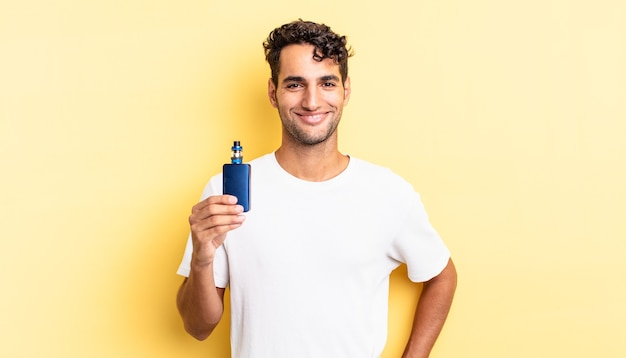 Hispanic handsome man smiling happily with a hand on hip and confident. vaporizer concept