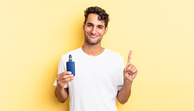 Hispanic handsome man smiling and looking friendly, showing number one. vaporizer concept