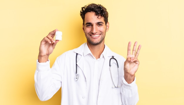Hispanic handsome man smiling and looking friendly, showing number three. physician bottle pills concept