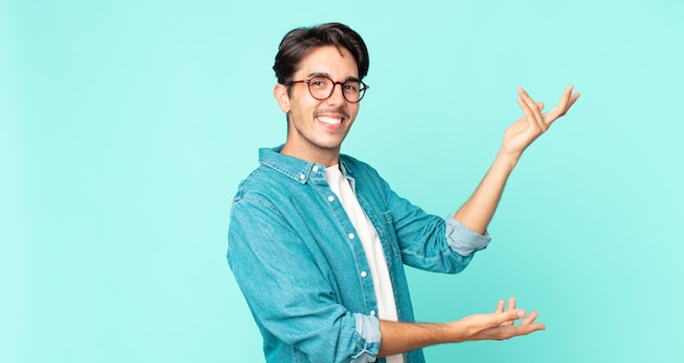 Латиноамериканский красавец улыбается гордо и уверенно, чувствует себя счастливым и довольным и демонстрирует концепцию на пространстве для копирования