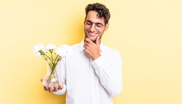 Испанский красавец улыбается с счастливым, уверенным выражением лица, положив руку на подбородок. цветочный горшок концепция