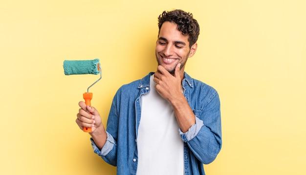 Испанский красавец улыбается с счастливым, уверенным выражением лица, положив руку на подбородок. роликовая краска