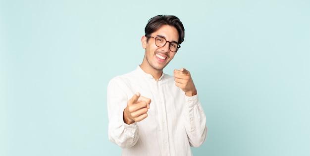 카메라를 가리키는 긍정적이고 성공적이고 행복한 태도로 웃고 있는 히스패닉 잘생긴 남자, 손으로 총기 기호 만들기