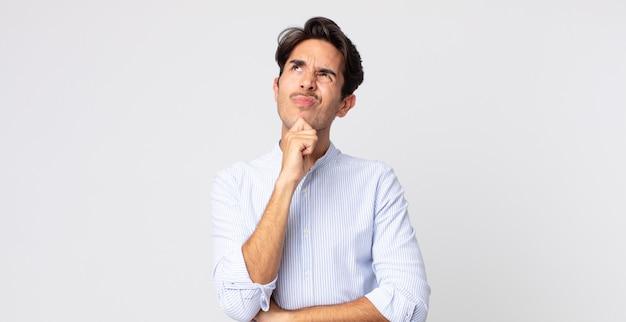ヒスパニック系のハンサムな男が考え、疑わしくて混乱し、さまざまな選択肢があり、どの決定を下すか疑問に思っています