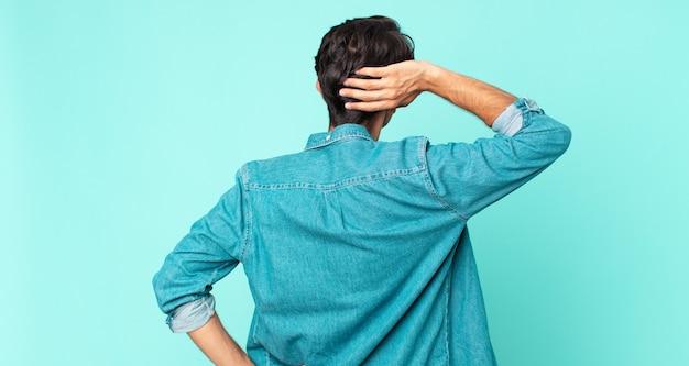 ヒスパニック系のハンサムな男が考えたり疑ったり、頭を掻いたり、困惑したり混乱したり、背面図または背面図