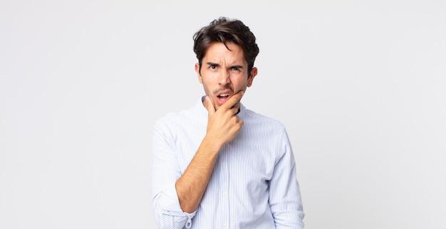 Латиноамериканский красавец с широко открытыми глазами и ртом, положив руку на подбородок, чувствуя неприятный шок, говорит что или вау