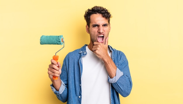 Hispanic handsome man with mouth and eyes wide open and hand on chin. roller paint concept
