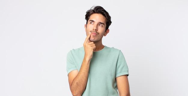 Латиноамериканский красавец с удивленным, нервным, встревоженным или испуганным взглядом, смотрящий в сторону в сторону места для копирования