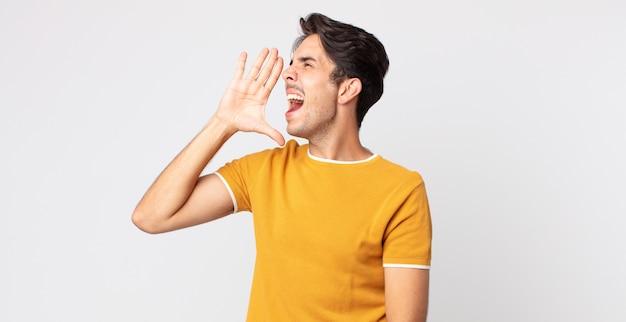 ヒスパニック系のハンサムな男が、口の横に手を置いて、横のスペースをコピーするために大声で怒って叫んでいます