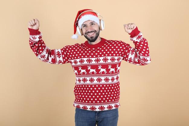 ヒスパニック系ラテンアメリカ人、サンタの帽子が黄色の背景に笑みを浮かべてクリスマスに