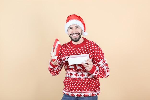 ヒスパニック系ラテンアメリカ人、クリスマスの帽子が贈り物を開く、ベージュの背景