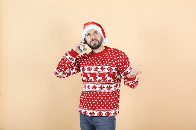携帯電話を使用してクリスマスの帽子をかぶったヒスパニック系ラテン系男性