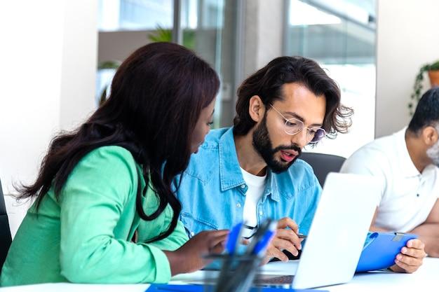 ヒスパニック系の男性とアフリカ系アメリカ人の女性がオフィスで一緒に働くビジネスコンセプトスタートアップ