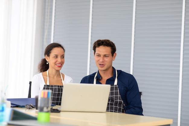 현대 홈 오피스에서 노트북 컴퓨터 작업을 하는 검은 앞치마를 입은 히스패닉 남녀 바리스타