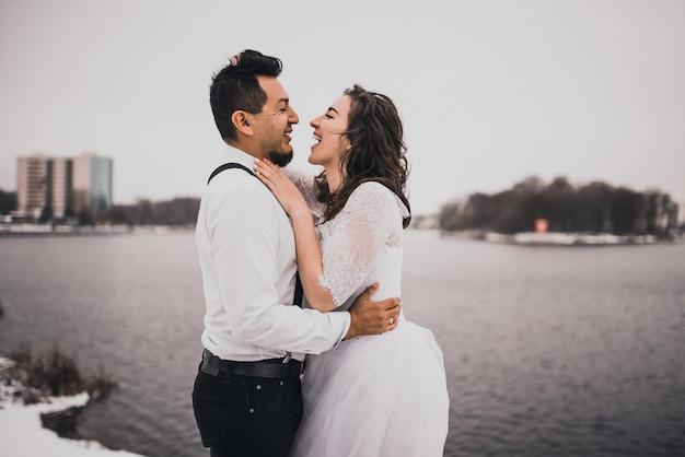 Испаноязычные мужчина и женщина обнимают жениха и невесту зимой в снегу