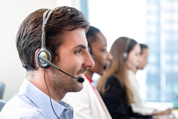 Hispanic man in call center office with team
