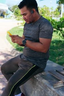 야외에서 훈련하는 동안 휴대 전화를 확인하는 히스패닉 남자