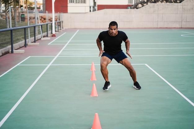 スピードと敏捷性のコーンドリルトレーニングセッションを屋外で行うヒスパニック系の男性