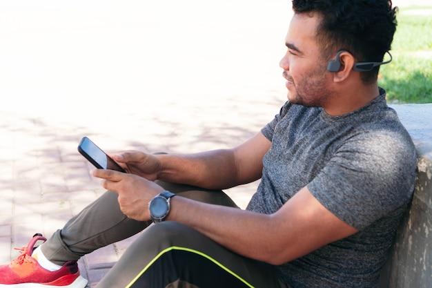 운동하는 동안 휴대 전화로 음악을 듣고 피트니스 옷을 입은 히스패닉 남자