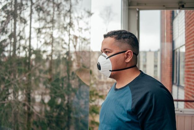 バルコニーの防護マスクのヒスパニック系の男。