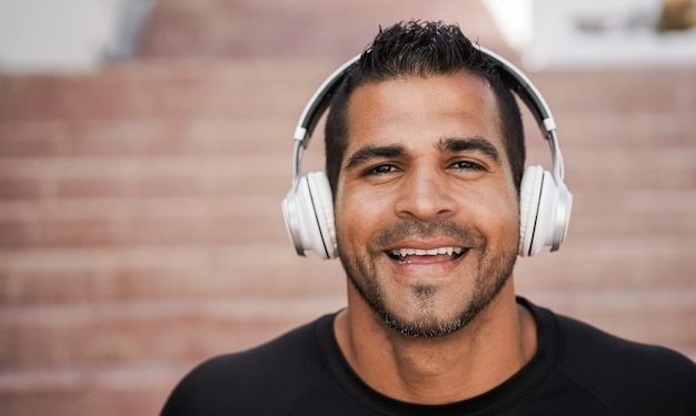 Испаноязычный мужчина слушает музыку в наушниках - сосредоточиться на лице