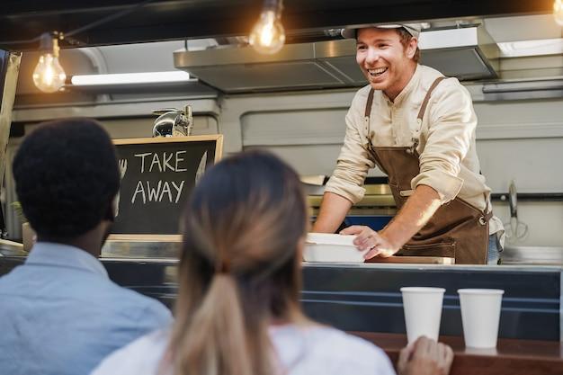 Hispanic man serving take away food inside food truck - focus on chef face